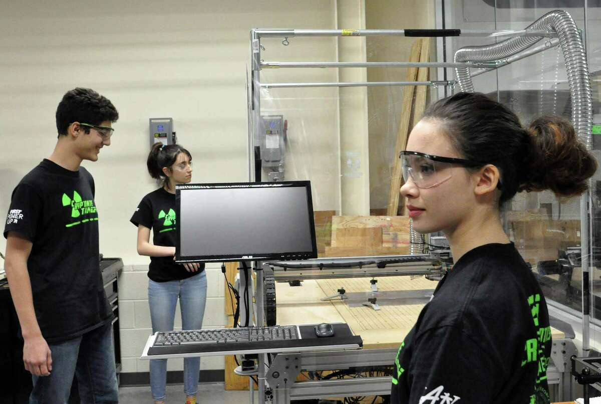 Cinco Ranch High School students Tejas George, Bella Riffle and Kyna McGill stand in front of a high-tech CNC cutting machine at a specal Katy Independent School District Science, Technology, Engineering and Mathematics center to support robotics teams entered in international competitions. The Cinco Ranch students are among 99 teens who joinedFIRST Robotics Team 624, known as CRyptonite.