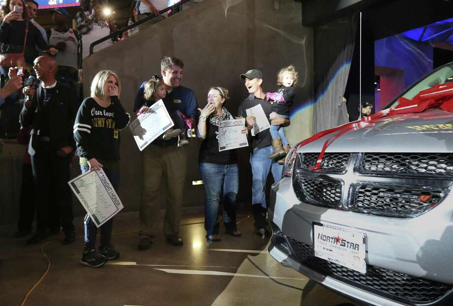 Sarah Merriman (left), whose husband is a soldier serving in Africa, appears shocked as she is given a new van during the Spurs's Military Appreciation Night at the AT&T Center on Wednesday, Mar. 21, 2018. The vehicle was provided by the nonprofit Wish for Our Heroes, which teamed up with USAA, Lone Star Auto Group and the San Antonio Spurs.  Merriman has endured a series of health problems while raising twin daughters. (Kin Man Hui/San Antonio Express-News) Photo: Kin Man Hui /San Antonio Express-News / ©2018 San Antonio Express-News