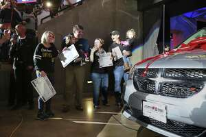 Sarah Merriman (left), whose husband is a soldier serving in Africa, appears shocked as she is given a new van during the Spurs's Military Appreciation Night at the AT&T Center on Wednesday, Mar. 21, 2018. The vehicle was provided by the nonprofit Wish for Our Heroes, which teamed up with USAA, Lone Star Auto Group and the San Antonio Spurs.  Merriman has endured a series of health problems while raising twin daughters. (Kin Man Hui/San Antonio Express-News)