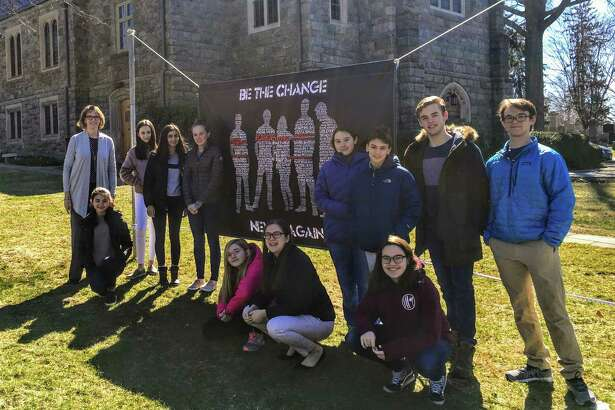 Members of First Congregational Church of Greenwich stand by the banner they designed in solidarity with survivors of a mass shooting in Parkland, Fla.