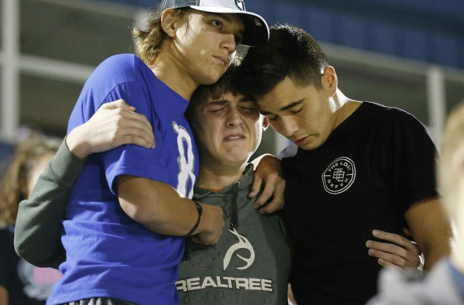 La Vernia High School students Derrick Barnhardt (right) and Chris Johnson (left) comfort Daniel Friesenhahn during a community memorial service at La Vernia High School's football stadium in the aftermath of the shooting tragedy at First Baptist Church in Sutherland Springs. Friesenhahn said they knew and were praying for one of the survivors who suffered gunshot wounds to his legs. The grants announced Thursday will help fund programs such as counseling services for children. Photo: Kin Man Hui /San Antonio Express-News / ©2017 San Antonio Express-News