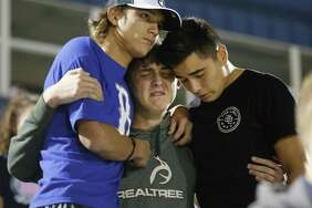 La Vernia High School students Derrick Barnhardt (right) and Chris Johnson (left) comfort Daniel Friesenhahn during a community memorial service at La Vernia High School's football stadium in the aftermath of the shooting tragedy at First Baptist Church in Sutherland Springs. Friesenhahn said they knew and were praying for one of the survivors who suffered gunshot wounds to his legs. The grants announced Thursday will help fund programs such as counseling services for children.