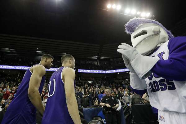 FILE - In this March 18, 2016, file photo, the Holy Cross mascot claps as player leave the court after a first-round men's NCAA college basketball game against Oregon in in Spokane, Wash. The president of the College of the Holy Cross says the Jesuit school will stop using the image of a knight as a logo and mascot even though trustees last month decided to keep the Crusaders athletic nickname. (AP Photo/Young Kwak, File)