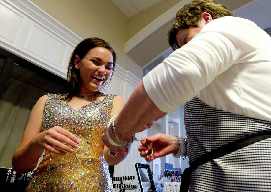 Kristen Smith shares a laugh as she tried on jewelry during the annual Priceless Gowns event at First Baptist Church, Thursday, March 22, 2018, in Conroe. The annual event provides Montgomery County girls more than 700 used and unused prom dresses to choose from free of charge. Photo: Jason Fochtman, Staff Photographer / © 2018 Houston Chronicle