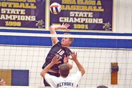 Edwardsville senior Cal Werths goes up for a kill during Thursday's season-opening match at Belleville Althoff.