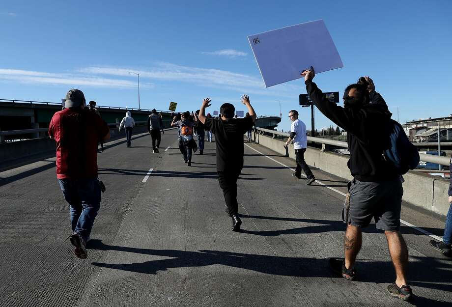 A Black Lives Matter protesters run onto Interstate 5 during a demonstration on March 22, 2018 in Sacramento, California.  Hundreds of protesters staged a demonstration against the Sacramento police department after two officers shot and killed Stephon Clark, an unarmed black man, in the backyard of his grandmother's house following a foot pursuit on Sunday evening.  (Photo by Justin Sullivan/Getty Images) Photo: Justin Sullivan/Getty Images