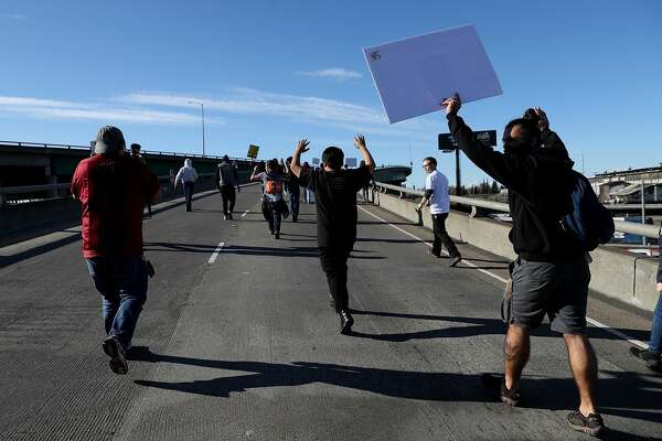 SACRAMENTO, CA - MARCH 22:  A Black Lives Matter protesters run onto Interstate 5 during a demonstration on March 22, 2018 in Sacramento, California.  Hundreds of protesters staged a demonstration against the Sacramento police department after two officers shot and killed Stephon Clark, an unarmed black man, in the backyard of his grandmother's house following a foot pursuit on Sunday evening.  (Photo by Justin Sullivan/Getty Images)