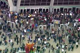 This photo from video provided by KCRA3 shows demonstrators protesting this week's fatal shooting of an unarmed black man mingling with fans outside Golden Center, just before tipoff of an NBA basketball game between the Atlanta Hawks and the Sacramento Kings in Sacramento, Calif., Thursday, March 22, 2018. Hundreds of people rallied for Stephon Clark, a 22-year-old who was shot Sunday in his grandparents' backyard. Police say they feared he had a handgun when they confronted him after reports that he had been breaking windows, but he only had a cellphone. (KCRA3 via AP)