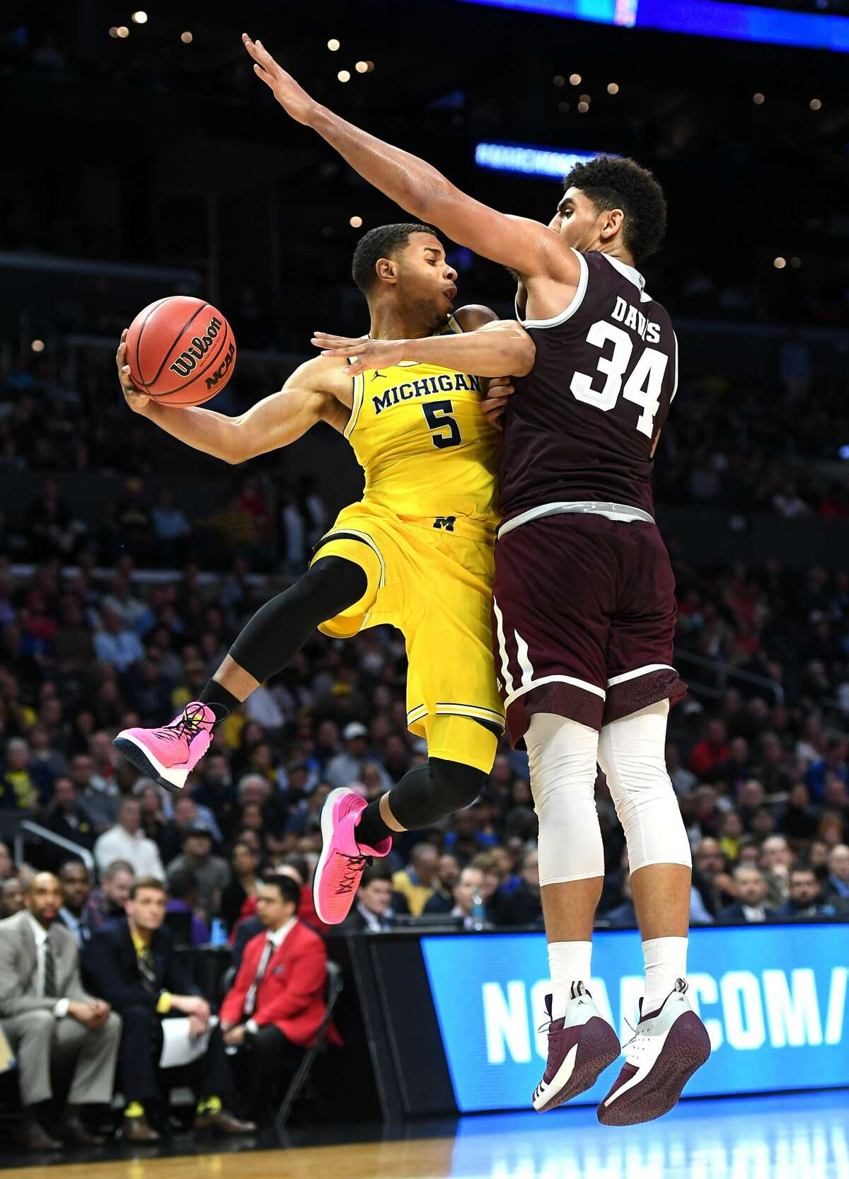 Michigan's Zavier Simpson gets a pass off in fornt of Texas A&M's Tyler Davis in the second half during an NCAA Tournament regional semifinal at Staples Center in Los Angeles on Thursday, March 22, 2018. Michigan advanced, 99-72. (Wally Skalij/Los Angeles Times/TNS)