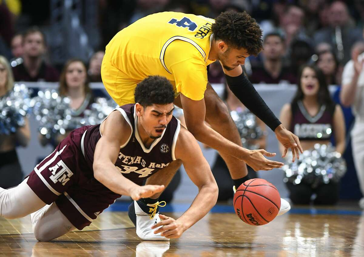 Michigan's Isaiah Livers, top, battles for a loose ball with Texas A&M's Tyler Davis in the second half during an NCAA Tournament regional semifinal at Staples Center in Los Angeles on Thursday, March 22, 2018. Michigan advanced, 99-72. (Wally Skalij/Los Angeles Times/TNS)