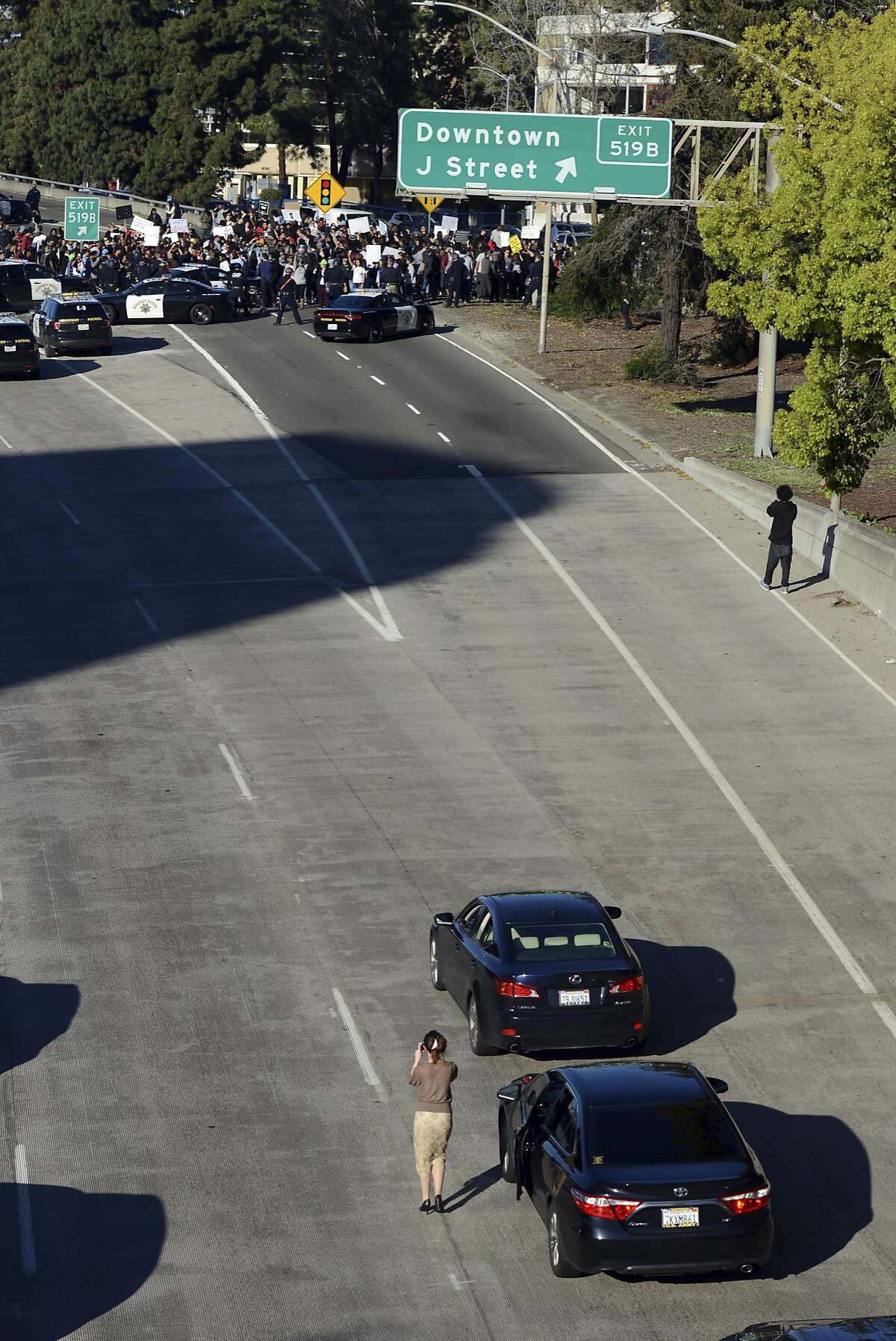 A motorist who stopped because of a demonstration photographs people protesting the fatal shooting of an unarmed black man, as they shut down Interstate 5 in Sacramento, Calif., Thursday, March 22, 2018. Hundreds of people rallied for Stephon Clark, a 22-year-old who was shot Sunday in his grandparents' backyard. Police say they feared he had a handgun when they confronted him after reports that he had been breaking windows, but he only had a cellphone. (AP Photo/Robert Petersen)