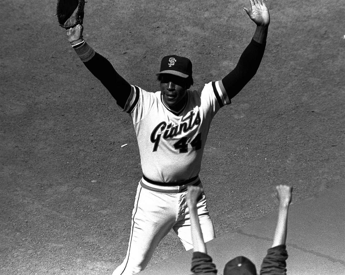 Willie McCovey of the San Francisco Giants raises his hands in salute to the cheering crowd after he was replaced in the lineup in a game with the Cincinnati Reds, July 3, 1980. It was the last home game appearance before retirement for the popular veteran. (AP Photo/RHH)