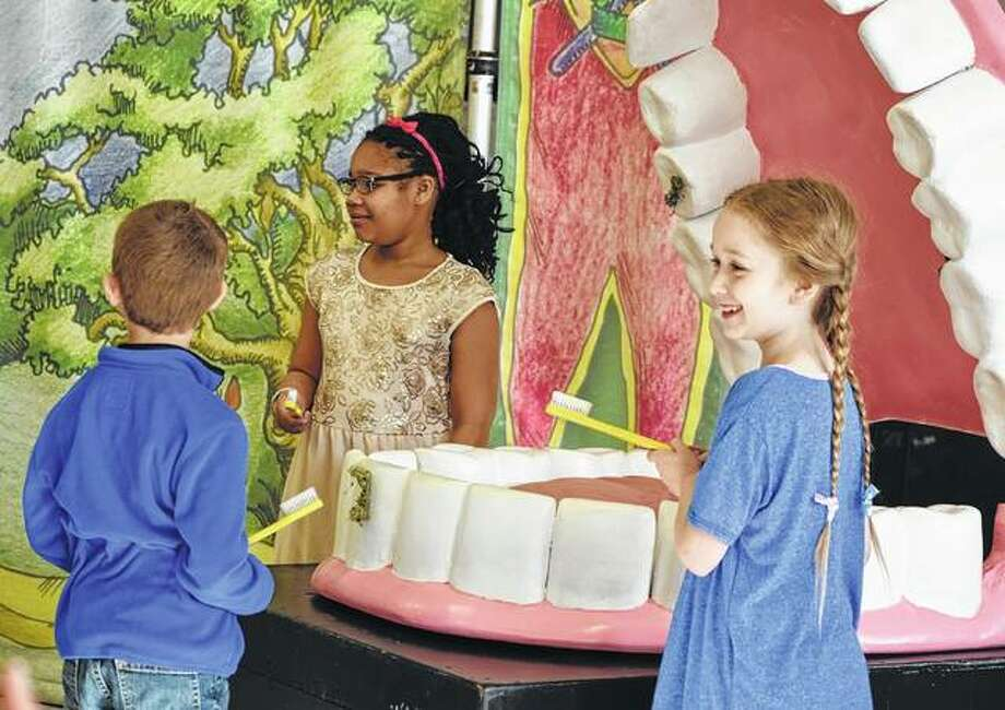 Murrayville-Woodson first-grader Kole Law (from left), third-grader Jaryah Thompson and second-grader Marley Coultas prepare Thursday to brush plaque from the teeth of a giant mouth during a program at the school. Photo: Samantha McDaniel-Ogletree | Journal-Courier