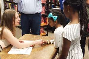 """Chelsea Clinton talks with Gabi James, 9, and her sister, Cami, 6, of  Sugar Land at Blue Willow Bookshop. Clinton signed her new book, """"She  Persisted Around the World,"""" at the store on Thursday, March 22, 2018."""
