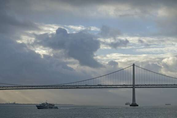 A break between storms appears behind the San Francisco-Oakland Bay Bridge as a Golden Gate Ferry makes its way across the bay Friday, March 2, 2018, in San Francisco. (AP Photo/Eric Risberg)