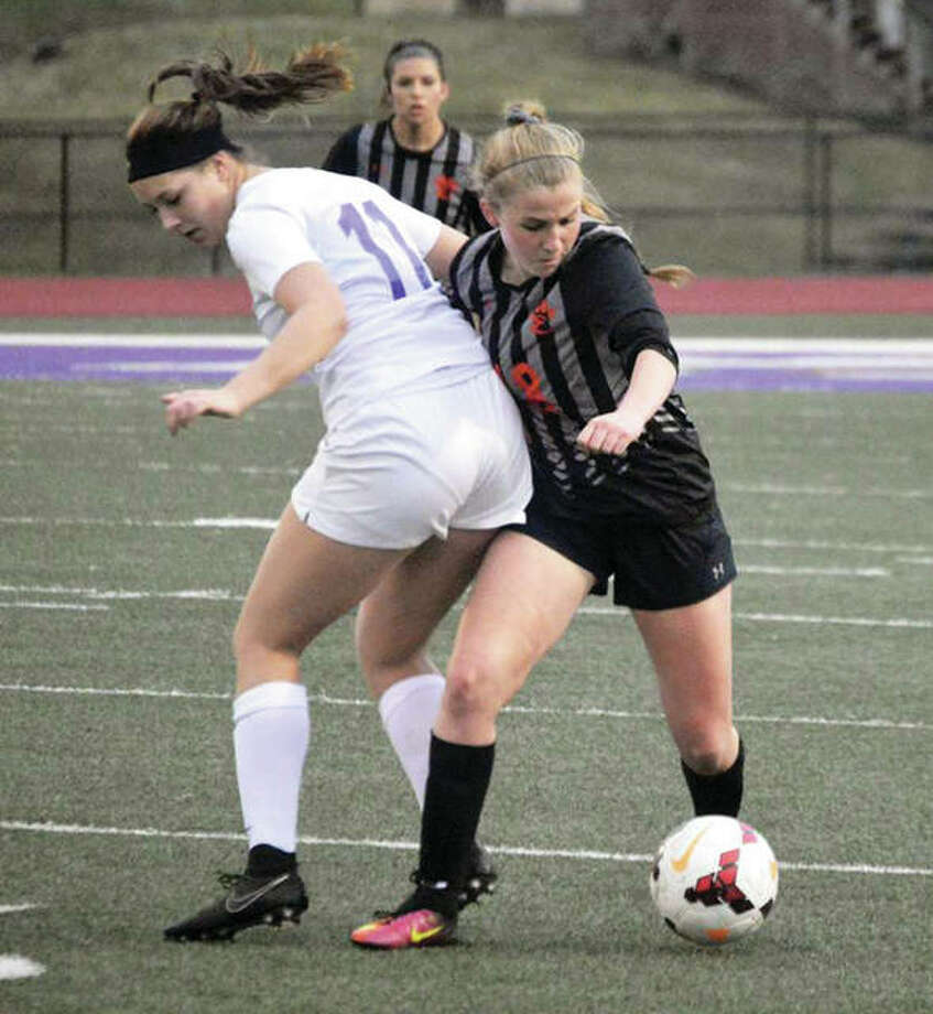 Edwardsville's Zoe Ahlers (right) battles with Collinsville's Alyssa Tucker for possession of the ball during the first half of Thursday night's SWC girls soccer match in Collinsville. The Tigers and Kahoks tied 4-4. Photo: Matthew Kamp / For The Telegraph