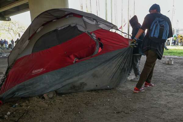 A man moves his belongings as city contractors conduct a cleanup of the Wheeler Homeless Encampment located under the US 59 Freeway, between Caroline Street and Almeda Road Friday, March 23, 2018, in Houston.