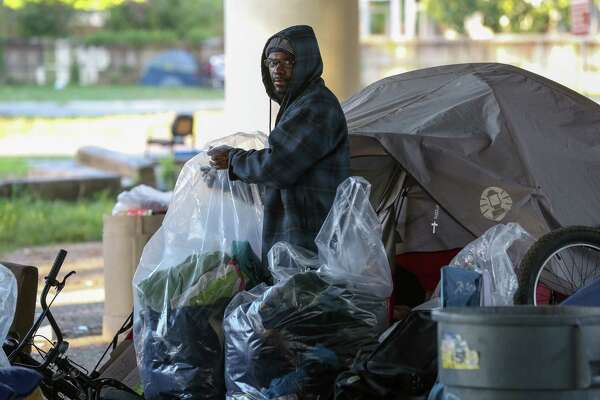 A man sorts through his belongings to move before city contractors conduct a cleanup of the Wheeler Homeless Encampment located under the US 59 Freeway, between Caroline Street and Almeda Road Friday, March 23, 2018, in Houston.