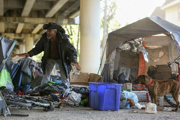 A man, better known as Trampus, finds a pair of shoes he wishes to keep while sorting through his belongings, before city contractors conduct a cleanup of the Wheeler Homeless Encampment located under the US 59 Freeway, between Caroline Street and Almeda Road Friday, March 23, 2018, in Houston.