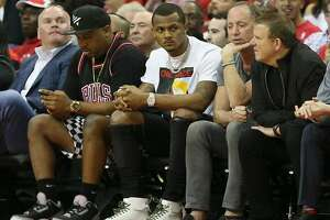 HOUSTON, TX - MARCH 22:  Deshaun Watson, center, of the Houston Texans looks on from court side at Toyota Center on March 22, 2018 in Houston, Texas. NOTE TO USER: User expressly acknowledges and agrees that, by downloading and or using this photograph, User is consenting to the terms and conditions of the Getty Images License Agreement.  (Photo by Bob Levey/Getty Images)