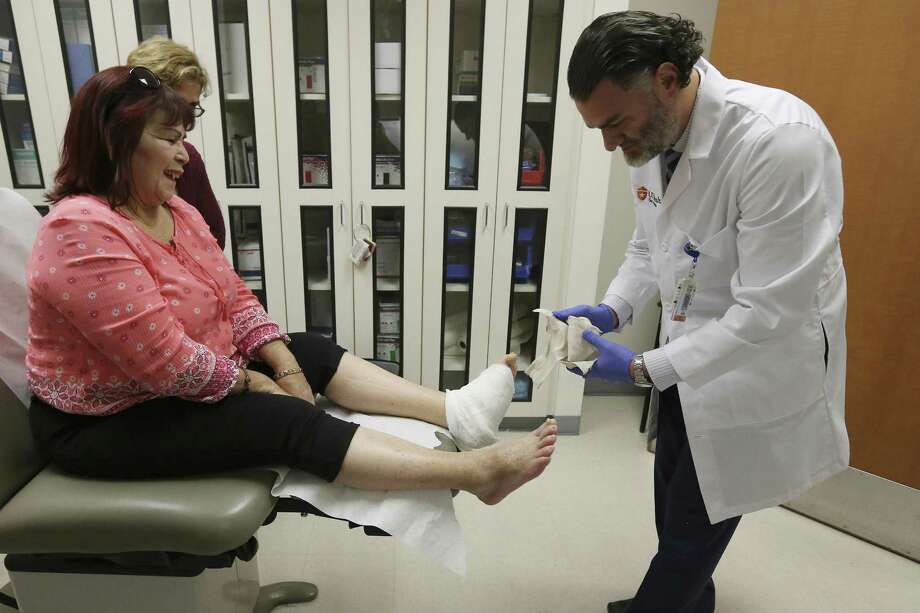 UT Health Podiatric Surgeon Dr. Thomas Zgonis visits with patient Luz Jimenz about the condition of her foot after surgery at the Preservation of Ambulation and Limb Salvage Clinic. Photo: Kin Man Hui / San Antonio Express-News / ©2018 San Antonio Express-News