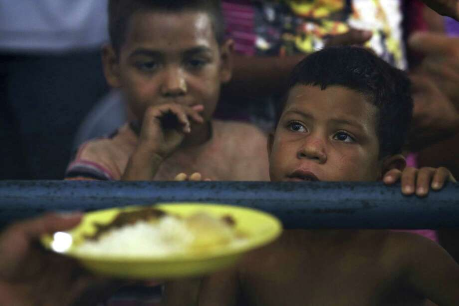 In this March 8, 2018 photo, Venezuelan children wait for a free meal at a migrant shelter set up at the Tancredo Neves Gymnasium in Boa Vista, Roraima state, Brazil. This is the largest of three shelters for migrants in the city, and has 700 people despite being equipped for 200. Photo: Eraldo Peres /Associated Press / Copyright 2018 The Associated Press. All rights reserved.