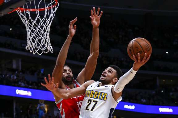 CORRECTS TO BRANDAN WRIGHT, NOT ANDERSON - Denver Nuggets guard Jamal Murray (27) goes up for a shot against Houston Rockets forward Brandan Wright (32) during the third quarter of an NBA basketball game, Sunday, Feb. 25, 2018, in Denver. (AP Photo/Jack Dempsey)