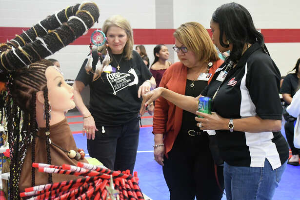 Linda Macias, associate superintendent of curriculum and instruction and accountability, views the winning projects at the district cosmetology competition along with Sharon Hogue, career and technical education coordinator, and Lynette Mosby, Langham Creek cosmetology instructor.