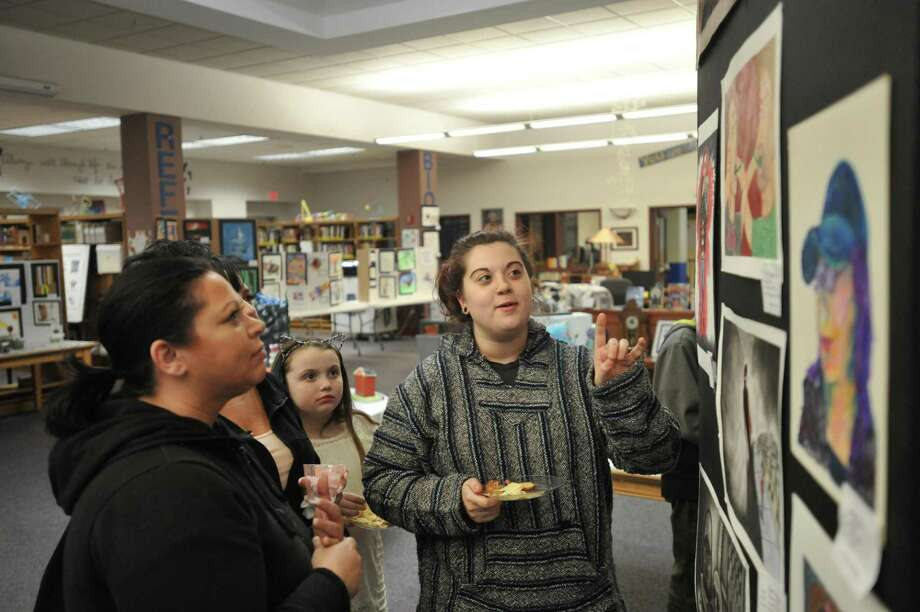 Students from The Gilbert School showed off the fruits of their creativity Thursday evening as part of the annual art show at the Winsted institution. Above, sophomore Elaina Brennan discusses her works with attendees. Photo: Ben Lambert / Hearst Connecticut Media /