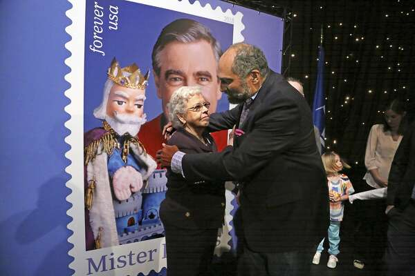 Fred Rogers wife, Mrs. Joanne Rogers, left, gets a hug from Pittsburgh Steelers Pro Football Hall of Fame running back Franco Harris in front of a giant Mister Rogers Forever Stamp following the first-day-of-issue dedication in WQED's Fred Rogers Studio in Pittsburgh, Friday, March 23, 2018. (AP Photo/Gene J. Puskar)