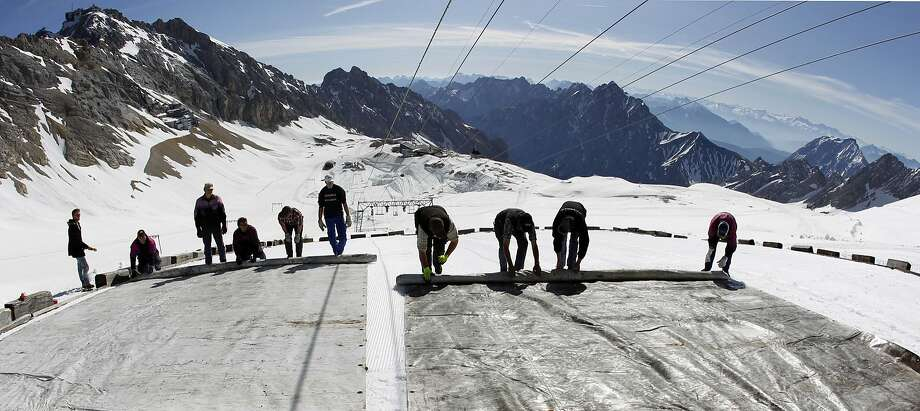 Workers cover a glacier with plastic sheets on Zugspitzein, Germany's highest peak, in a bid to keep it from melting. Photo: Matthias Schrader, AP