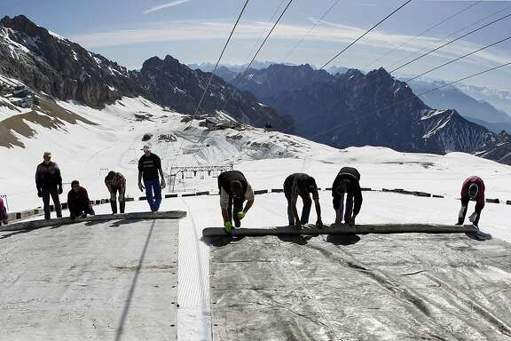 Workers cover a glacier with plastic sheets on Zugspitzein, Germany's highest peak, in a bid to keep it from melting.
