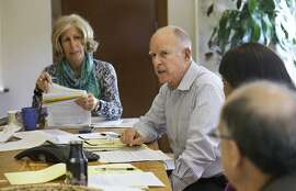 FILE - In this Monday, Sept. 29, 2014 file photo, Gov. Jerry Brown discusses a bill with advisor Nancy McFadden, left, at his Capitol office in Sacramento, Calif. McFadden, the chief of staff to   Brown, has died. She was 59. Brown's office says McFadden died Thursday, March 22, 2018, after a long battle with ovarian cancer. (AP Photo/Rich Pedroncell, File)