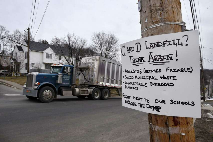 A tractor trailer moves past a sign protesting the Dunn C&D Landfill on Partition Street on Wednesday, March 21, 2018, in Rensselaer, N.Y. The truck was leaving the landfill after dumping its load of garbage there. (Will Waldron/Times Union)