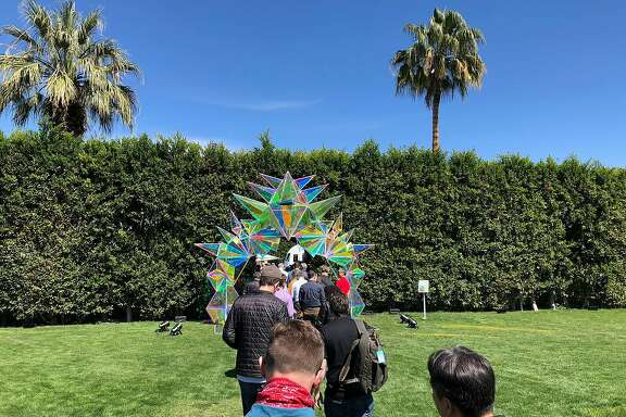 Guests pass under a 16-foot plexiglass archway coated in a reflective dichroic film during the Mars conference at the Parker Palm Springs hotel in Palm Springs, Calif., March 19, 2018. For Mars, an exclusive three-day conference run by Amazon for some of the world�s most successful geeks, the company  handpicked the roughly 200 attendees, most from the fields of artificial intelligence, robotics and space. (Jack Nicas/The New York Times)