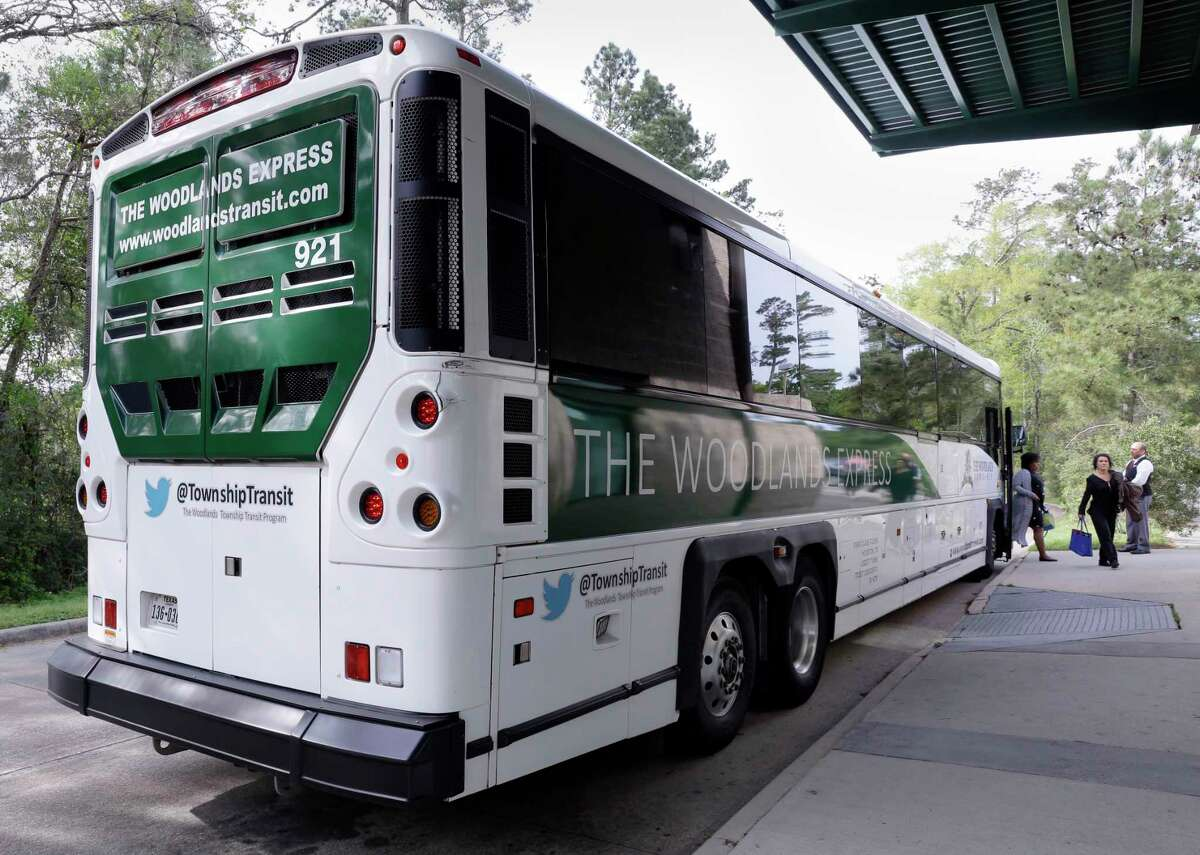 Communters exit one of the buses of The Woodlands Express, a commuter bus service to Houston, at the Marisco Place