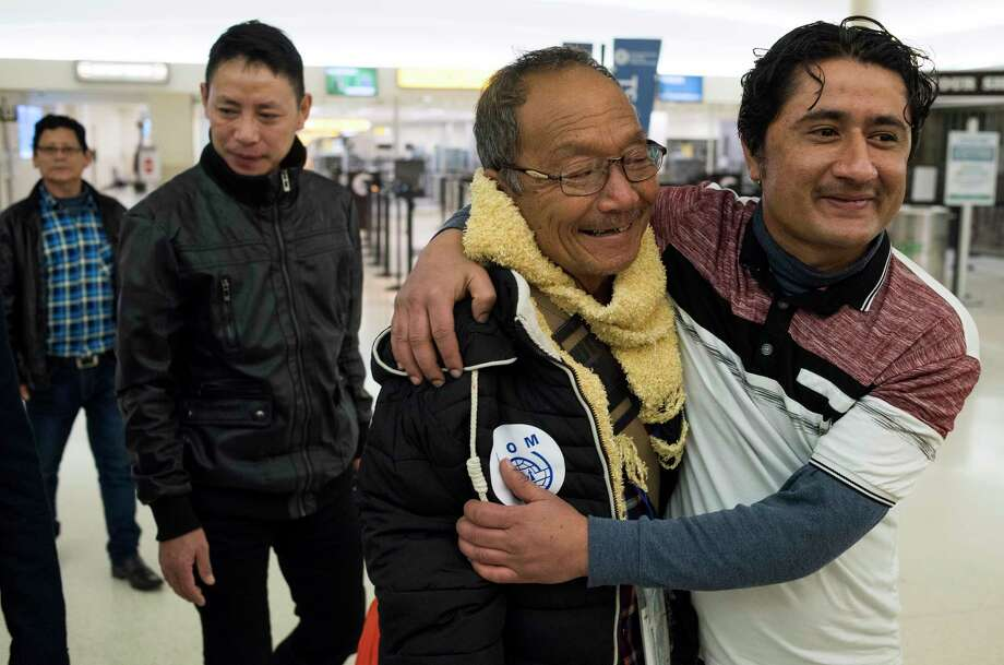 Kamal Sharma, right, of Columbus, embraces his relative Til Gurung, a Bhutanese refugee from Nepal, as he and other relatives arrive at the John Glenn Columbus International Airport in Columbus, Ohio on Thursday, Feb. 15, 2018. Two families of Bhutanese refugees met with their family members at the Columbus Airport after an 18 hour flight from Nepal where the families lived in the Beldangi Refugee Camp in Jhumpa, Nepal. Bhutanese refugees, most who are Buddhist or Hindu and were expelled during a government-led ethnic cleansing campaign against ethnic Nepalis in the early 1990s. (AP Photo/Ty Wright) Photo: Ty Wright / FR170125 AP