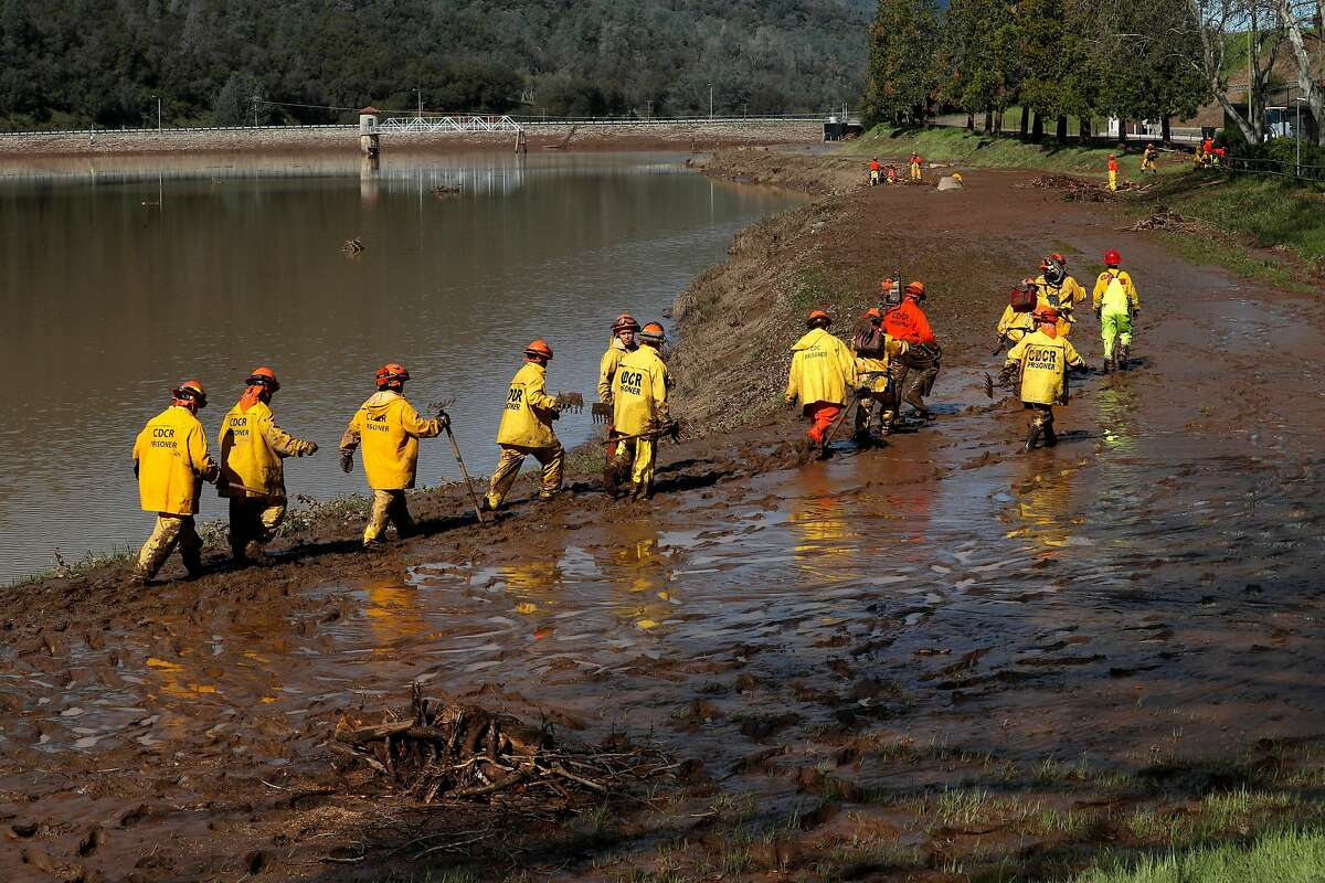 Inmate firefighters from Baseline Camp help with the debris clean up of Moccasin reservoir, in Moccasin, Calif., as seen on Fri. March 23, 2018. Officials issued a flash flood warning Thursday for south central Tuolumne County due to �imminent dam failure� at Moccasin Reservoir Dam in Tuolumne County.