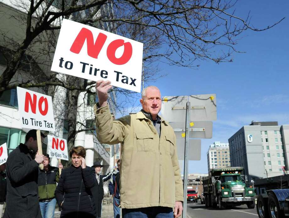 """Holding a sign that reads """"No to Tire Tax,"""" Shelton Mayor Mark Lauretti at the protest against tolls, a new gas tax and tire tax in Stamford in February. Lauretti said """"we have to make Connecticut more affordable, we are pricing everyone out of the state."""" As the state grapples with a growing deficit and looks to impose new taxes on its residents, Lauretti is promising a 10th year of no tax increases in Shelton. Photo: Bob Luckey Jr. / Hearst Connecticut Media / Greenwich Time"""
