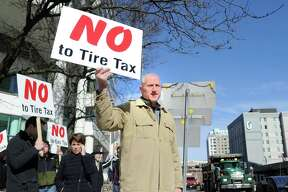 "Holding a sign that reads ""No to Tire Tax,"" Shelton Mayor Mark Lauretti at the protest against tolls, a new gas tax and tire tax in Stamford in February. Lauretti said ""we have to make Connecticut more affordable, we are pricing everyone out of the state."" As the state grapples with a growing deficit and looks to impose new taxes on its residents, Lauretti is promising a 10th year of no tax increases in Shelton."
