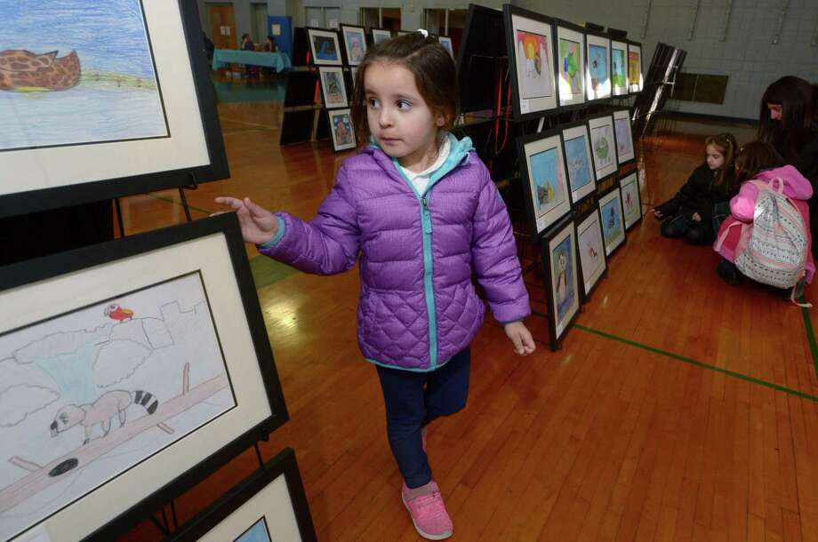Students from All Saints Catholic School including Pre-Kindergartner Sofia Bonfim peruse the artwork at the schools 3rd annual Art Show on Friday, in Norwalk. Photo: Erik Trautmann / Hearst Connecticut Media / Norwalk Hour