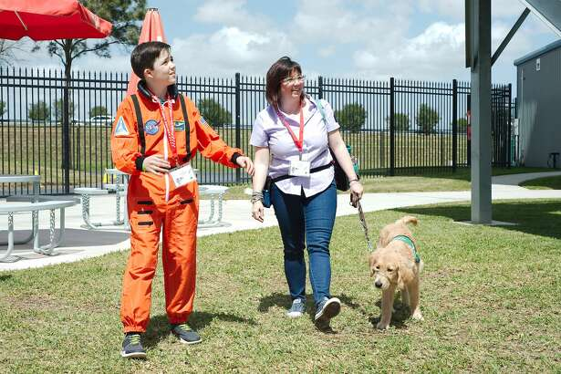 Guide Dogs for the Blind organization volunteers Mandy and Harrison Biggers   tour Space Center Houston with their guide dog in training Allegra as the young dog learns about crowds and public spaces Friday, Mar. 23.