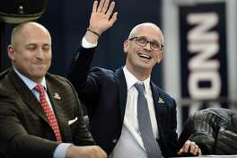 Dan Hurley waves as he is introduced as the new UConn men's basketball coach on Friday in Storrs. Hurley, who coached Rhode Island into the NCAA Tournament the past two seasons, replaces Kevin Ollie, who was fired earlier this month. At left is UConn Athletic Director David Benedict.