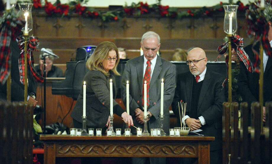 Linda Autore, Execuetive Director of Laurel House, lights one of 13 candles representing those who have died homeless in our community during a service at the First Congregational Church in Stamford, Conn. on Thursday, Dec. 21, 2017 on National Homeless Persons' Memorial Day 2017. Also pictured are Ludwig Spinelli, Execuetive Director of Optimus Health Care and Rafael Pagen, Excuetive Director of Pacific House. Photo: Matthew Brown / Hearst Connecticut Media / Stamford Advocate