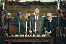 Linda Autore, Execuetive Director of Laurel House, lights one of 13 candles representing those who have died homeless in our community during a service at the First Congregational Church in Stamford, Conn. on Thursday, Dec. 21, 2017 on National Homeless Persons' Memorial Day 2017. Also pictured are Ludwig Spinelli, Execuetive Director of Optimus Health Care and Rafael Pagen, Excuetive Director of Pacific House.
