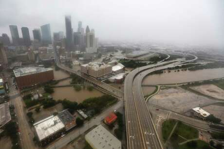 Downtown Houston is shown with Buffalo Bayou rising with floodwaters from Tropical Storm Harvey on Monday, Aug. 28, 2017, in Houston. ( Brett Coomer / Houston Chronicle )