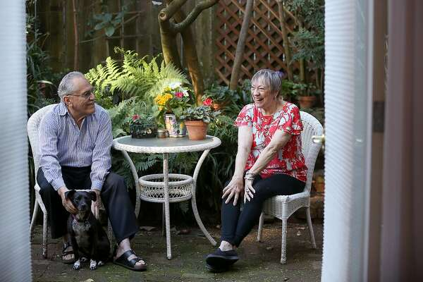 Airbnb hosts Rodolfo Cancino and his wife Karen Cancino with Indy in their backyard looking through the airbnb bedroom doors on Friday, February 16, 2018, in San Francisco, Ca.