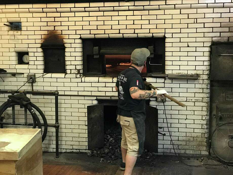 A pizza maker at the coal-fired oven at Frank Pepe Pizzeria Napoletana in New Haven. Photo: Greg Morago / Hearst