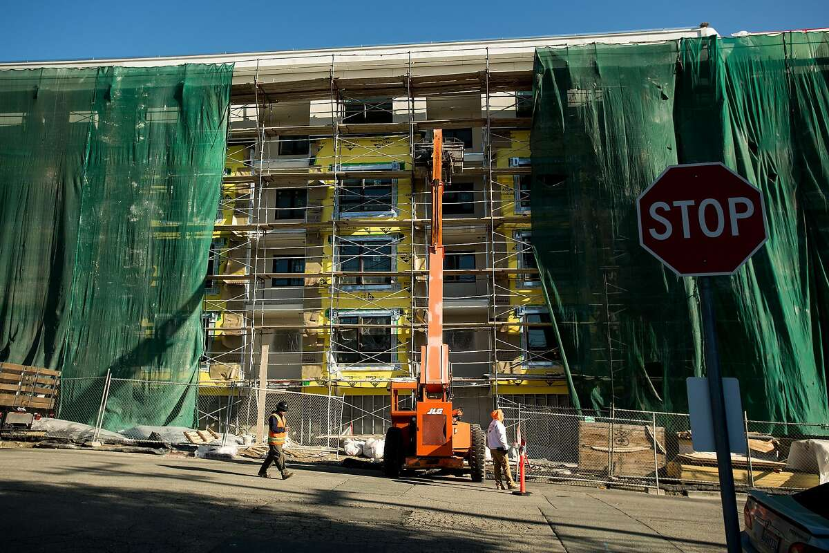 A construction worker passes the Vaya housing complex, a 178 unit transit-oriented development slated to open this year.