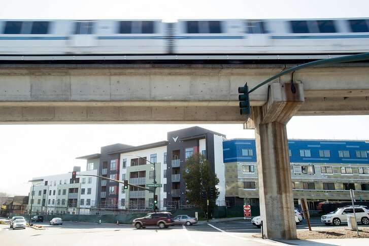 A BART train passes the Vaya housing project, a 178 unit transit-oriented development slated to open this year in Walnut Creek, Calif. A bill to increase housing development near BART stations squeaked past the state Senate on Thursday.